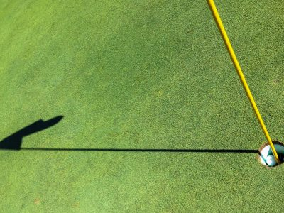 Golf ball in cup / hole on the green with flagstick and shadow.